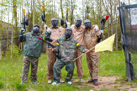 Team of five men with flag play paintball