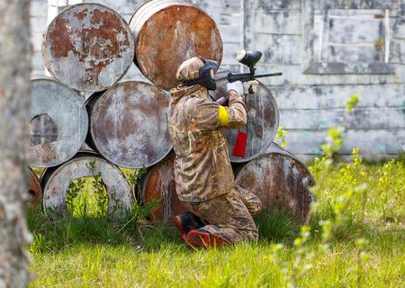 ambush: Paintball sportsman in ambush behind rusty barrels