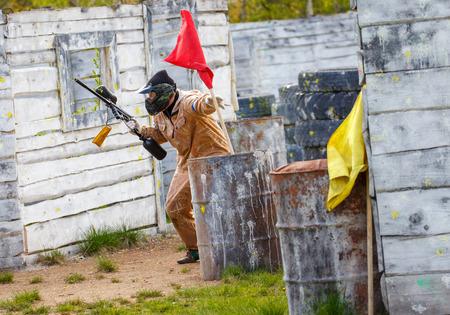 Вооруженный человек настройке флаг победы в пейнтбол миссии