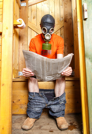 Man in respirator reading newspaper in wooden village WC