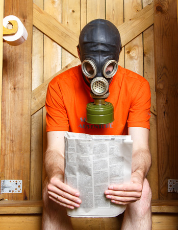 gasmask: Man in gas-mask sitting in toilet with newspaper