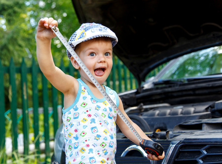 bonnet: Funny kid with tape near open car bonnet Stock Photo