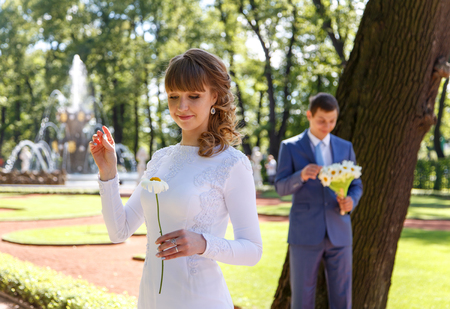 tell fortunes: Young bride tears off chamomile petals to tell fortunes