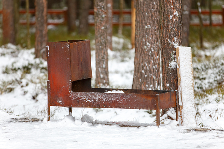 Welded: Huge steel welded brazier on snow in forest