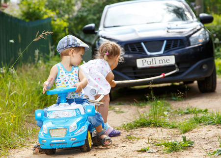 Маленький мальчик и девочка хотите, чтобы перетащить реальный автомобиль