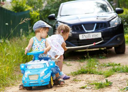 Mały chłopiec i dziewczyna chce przeciągnąć prawdziwy samochód Zdjęcie Seryjne