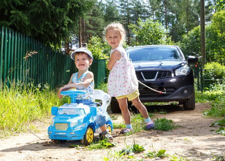 pull toy: Dos ni�os divertidos tratando de remolcar coche real por la cuerda