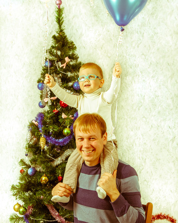 celebrate year: Young father with little son on his shoulders near New Year fir. Retro style photo.