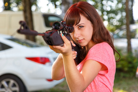 telescopic: Cool female sniper aiming from telescopic rifle Stock Photo