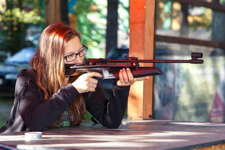 Смарт девушка стрельба из пневматического оружия Фото со стока