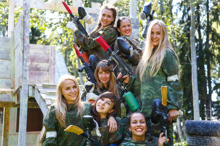 Group of smiling young girls with paintball ammunition Фото со стока