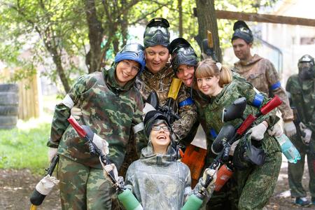 Uśmiechnięta grupa graczy paintballowych plenerze