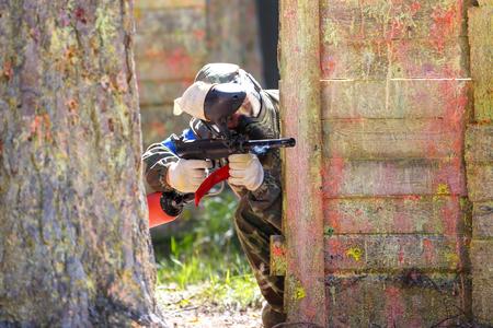 Człowiek w kamuflażu strzelania z pistoletu do paintballa