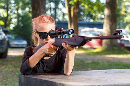 telescopic: Cool blond in sun glasses aiming from telescopic gun Stock Photo
