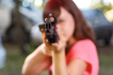gun sight: Young woman shooting from telescopic air gun, focus on front sight Stock Photo