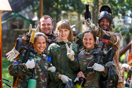 Happy team of five paintball players outdoors Фото со стока