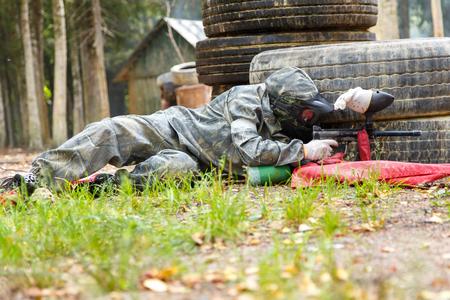 ambush: Man lying in ambush with paintball marker