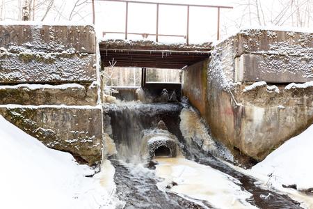ice dam: Water stream through the river dam in winter