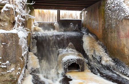 ice dam: Concrete lake weir with non-freezing water stream in winter