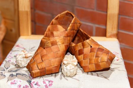 bast: National Russian bast shoes on brick background