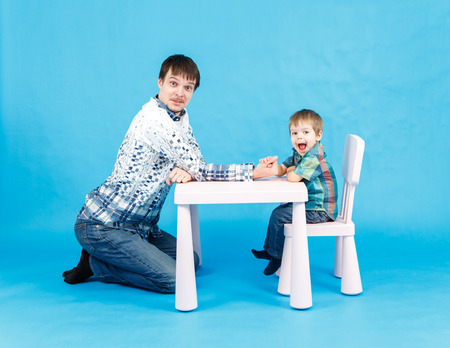 male arm: Funny father and little son competing in arm wrestling on blue background Stock Photo