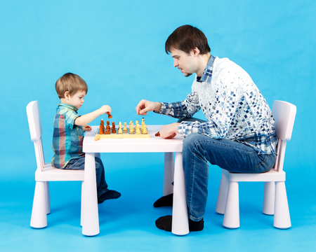 Playing chess with dad - little boy and his father on blue background Stock Photo