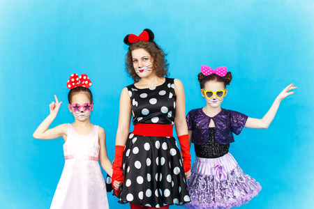 role models: Glamour woman and two girls in party costumes on blue background Stock Photo