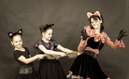episode: Episode of funny play in retro style. Three girls in cat costumes on black background.