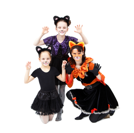 role models: Young woman and two girls in cat carnival costumes posing Stock Photo
