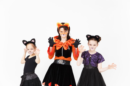 catsuit: Young woman and two girls in cat carnival costumes posing Stock Photo