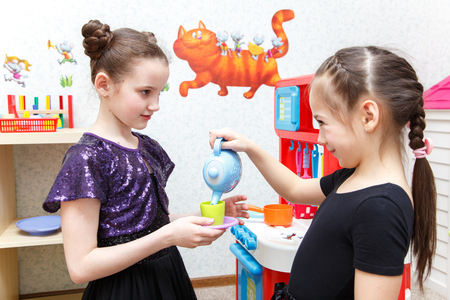 role play: Two little girls play role game with toy kitchen in day care center Stock Photo