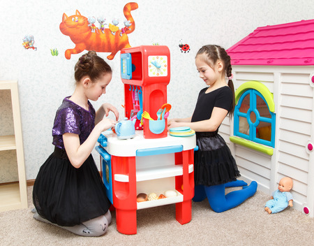day care center: Two little girls play role game with toy kitchen in day care center Stock Photo