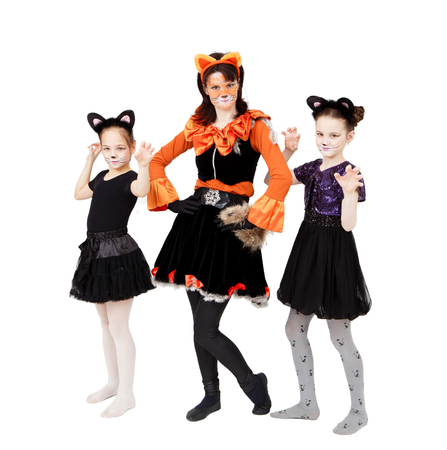 Young woman and two girls in cat carnival costumes posing Фото со стока