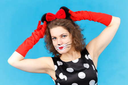 likeness: Attractive girl in likeness of cat on blue background posing