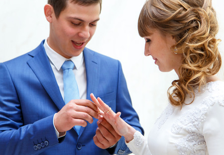 fingers put together: Bride and groom exchange wedding rings at ceremony in wedding palace