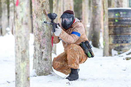 fortification: Paintball game in winter. Cool shooter behind fortification. Stock Photo