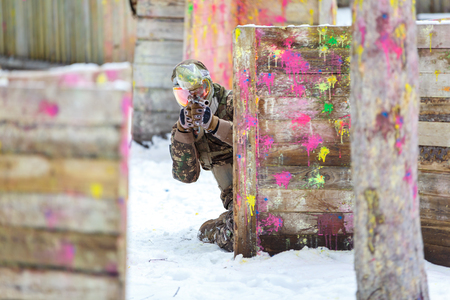 Paintball game in winter. Cool shooter behind fortification. Banque d'images