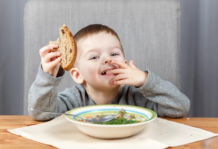 comiendo pan: Niño feliz que come el pan para la cena Foto de archivo