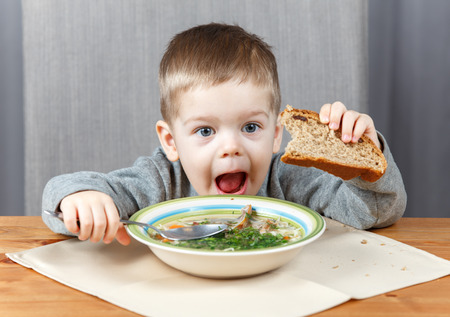 a little dinner: Funny little kid with plate of soup for dinner