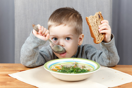 a little dinner: Little boy eating soup for dinner