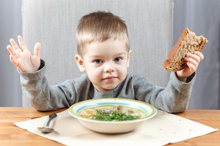 comiendo pan: Niño pequeño y su sopa para la cena