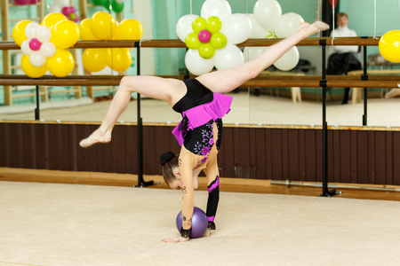 splits: Young female gymnast doing crafty splits on art gymnastics competitions