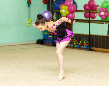 crafty: Young female gymnast doing crafty trick with ball on art gymnastics performance