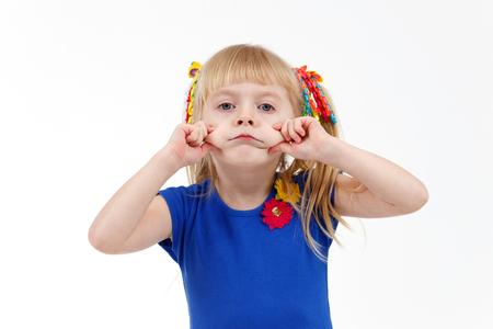 Забавный маленький блондин дошкольника с двумя хвостами делает печальную гримасу