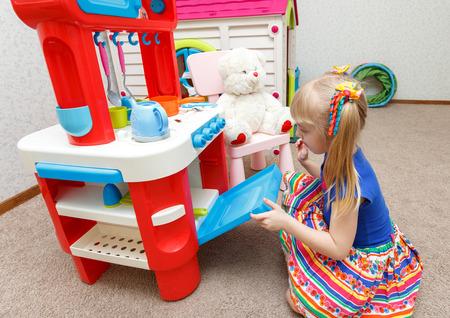 Трудолюбивый маленькая девочка, приготовления пищи в игрушечном печи для ее плюшевого мишку Фото со стока