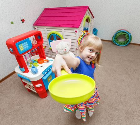 Симпатичная маленькая девочка, играя с игрушкой блюд в детском саду Фото со стока