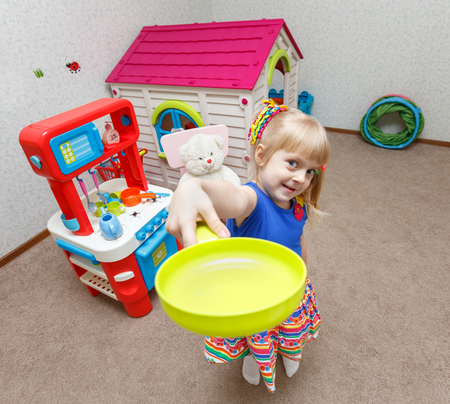 Cute little girl playing with toy dishes in daycare