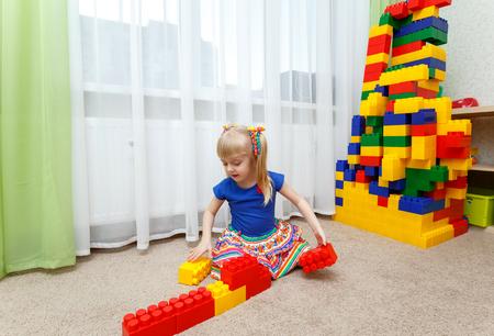 Довольно блондинка девочка играет с цветными блоками в детском саду Фото со стока