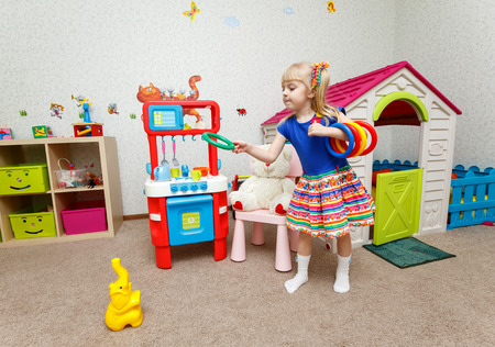 Funny little girl throwing plastic rings on toy elephant