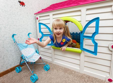Очень маленькая девочка, глядя из игрушечного домика в детском саду